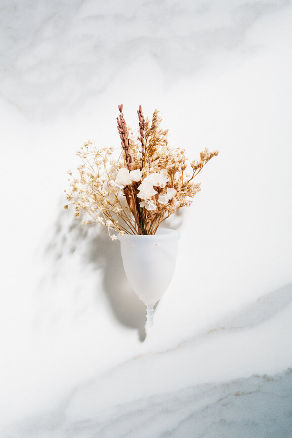 Menstrual cup cointaining dry flowers in a natural hard light. The cup is placed in front of a marble background.
