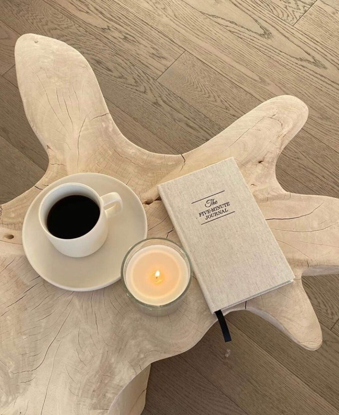 five minute journal flatlay on wooden table with coffee cup and candle