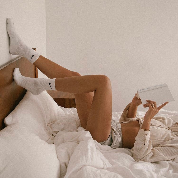 girl lounging in bed and reading a book