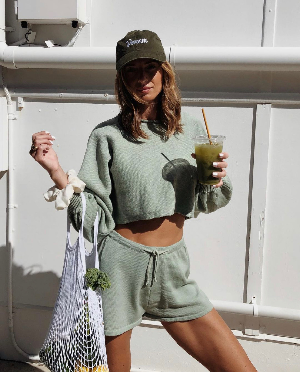 girl holding green juice and grocery bag