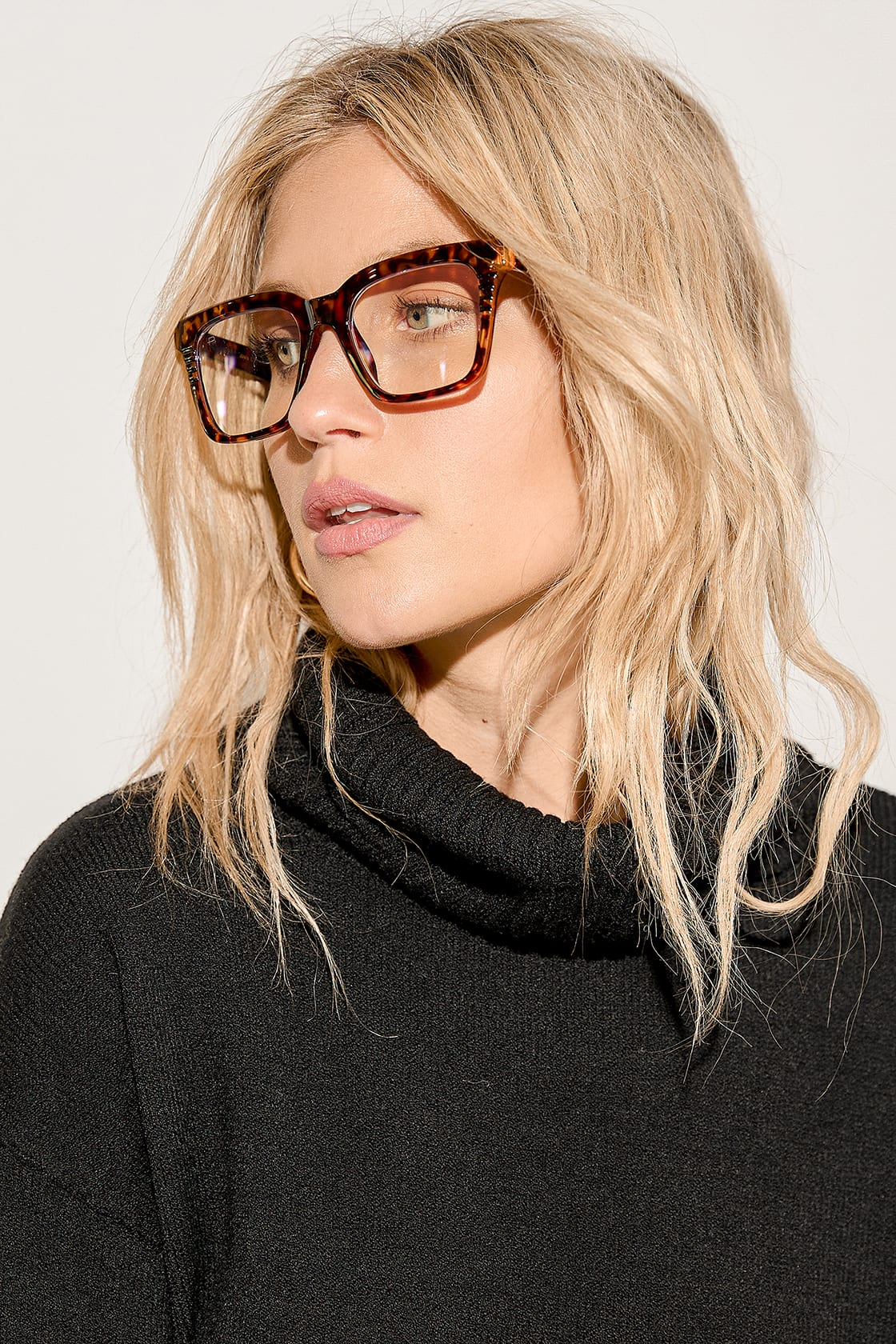 blonde woman wearing tortoise shell blue light glasses