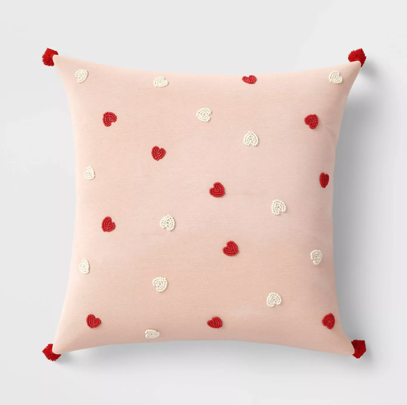 pink velvet pillow with white and red hearts and red tassels