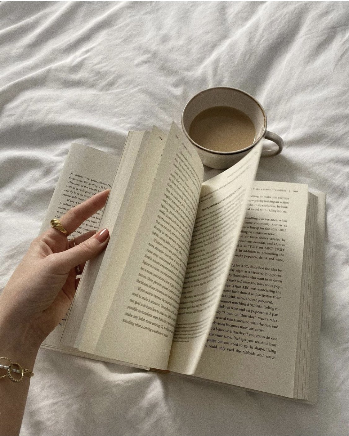 novel with coffee on bed