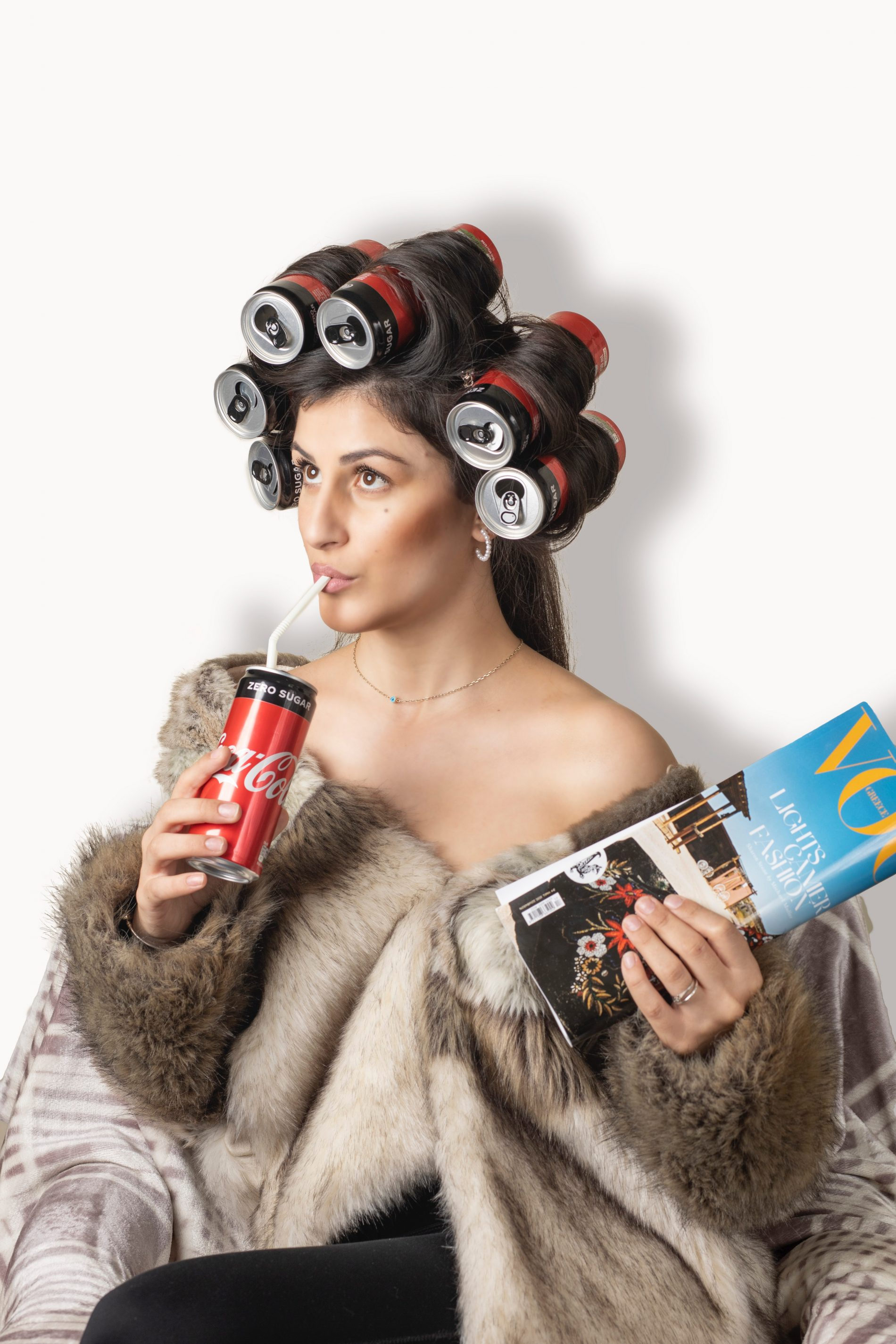 girl sipping on coke with coke cans as hair rollers