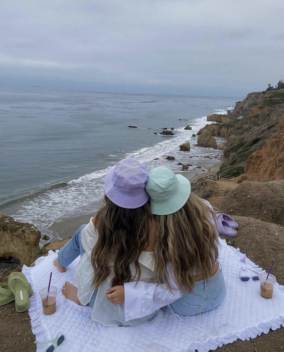 two influencers in bucket hats overlooking a cliff in malibu